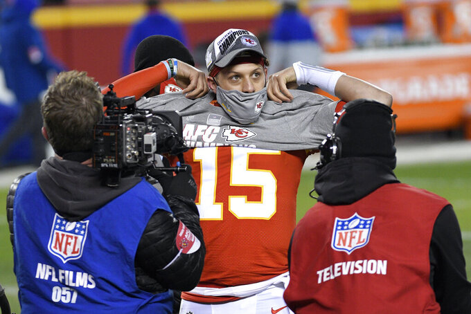 Kansas City Chiefs quarterback Patrick Mahomes puts a shirt on as he celebrates at the end of the AFC championship NFL football game against the Buffalo Bills, Sunday, Jan. 24, 2021, in Kansas City, Mo. The Chiefs won 38-24. (AP Photo/Reed Hoffmann)