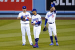 Los Angeles Dodgers' Yoshi Tsutsugo, left, Mookie Betts, center, and Chris Taylor stand in the outfield during a pitching change in the sixth inning of a baseball game against the Arizona Diamondbacks Thursday, May 20, 2021, in Los Angeles. (AP Photo/Mark J. Terrill)