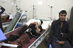 Wounded men receive treatment at a hospital after a bomb blast in Nangarhar, province east of Kabul, Afghanistan, Monday, Oct. 7, 2019. An afghan official says a bomb blast in eastern Nangarhar province has killed at least 10 people, including a child. Ataullah Khogyani, the governor's spokesman, said over 20 other people were wounded in the attack targeting a minibus carrying new army recruits in Jalalabad city. (AP Photo/Wali Sabawoon)