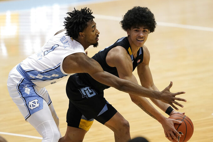 North Carolina guard Leaky Black (1) guards Marquette guard D.J. Carton during the second half of an NCAA college basketball game in Chapel Hill, N.C., Wednesday, Feb. 24, 2021. (AP Photo/Gerry Broome)