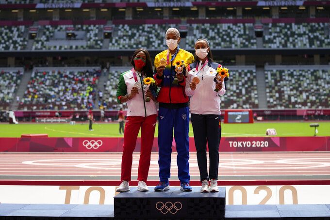 Gold medalist, Yulimar Rojas, centre, of Venezuela, stands with silver medalist Patricia Mamona, left, of Portugal, and bronze medalist Ana Peleteiro, of Spain, following the women's triple jump at the 2020 Summer Olympics, Monday, Aug. 2, 2021, in Tokyo. (AP Photo/Francisco Seco)