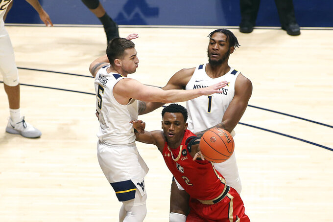 Northeastern guard Tyson Walker (2) passes while defended by West Virginia guard Jordan McCabe (5) and forward Derek Culver (1) during the second half of an NCAA college basketball game Tuesday, Dec. 29, 2020, in Morgantown, W.Va. (AP Photo/Kathleen Batten)