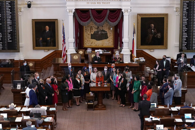 FILE - In this May 5, 2021, file photo, Texas state Rep. Donna Howard, D-Austin, center at lectern, stands with fellow lawmakers in the House Chamber in Austin, Texas, as she opposes a bill introduced that would ban abortions as early as six weeks and allow private citizens to enforce it through civil lawsuits, under a measure given preliminary approval by the Republican-dominated House. The law went into effect on Sept. 1. (AP Photo/Eric Gay, File)