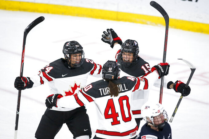 Canada's Melodie Daoust, right, celebrates her goal against the United States with Natalie Spooner, left, and Blayre Turnbull during the first period of an IIHF women's world hockey championships game Thursday, Aug. 26, 2021, in Calgary, Alberta. (Jeff McIntosh/The Canadian Press via AP)