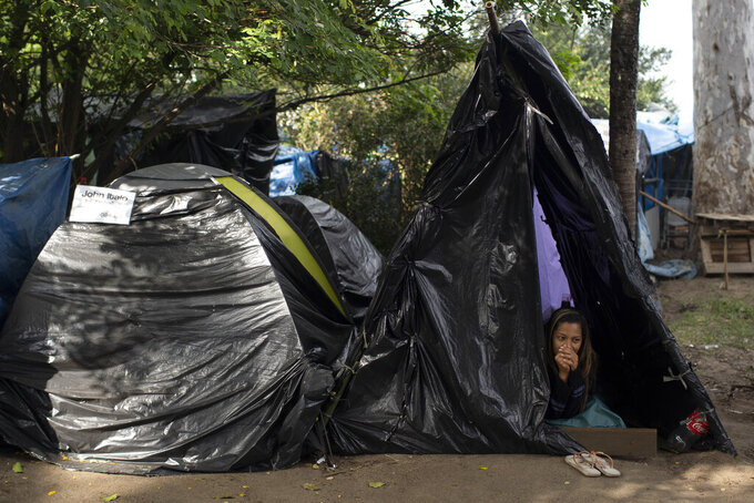 """FILE - In this May 26, 2021 file photo, a woman rests in a tent on land designated for a Petrobras refinery, called the """"First of May Refugee Camp,"""" which refers to the date the squatters camp sprung up during the new coronavirus pandemic in Itaguai, Rio de Janeiro state, Brazil. In the first quarter of 2021, Brazil saw its highest unemploymentand economic inequality in at least nine years, with the cost of living surging and tent cities and shantytowns emerging. (AP Photo/Silvia Izquierdo, File)"""