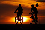 A pair of cyclists cross an empty downtown street as the sun sets Wednesday, April 1, 2020, in Kansas City, Mo. (AP Photo/Charlie Riedel)