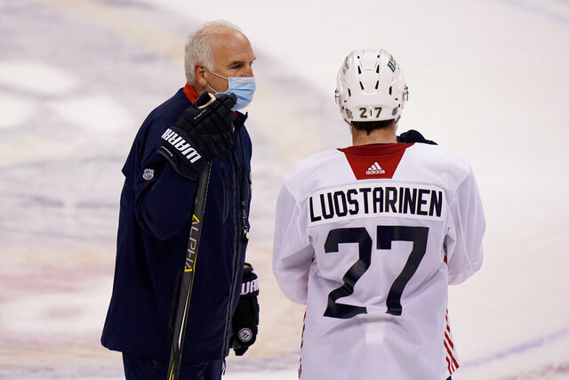 Florida Panthers head coach Joel Quenneville, left, talks with center Eetu Luostarinen (27) during NHL hockey training camp, Tuesday, Jan. 5, 2021, in Sunrise, Fla. (AP Photo/Lynne Sladky)