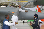 Indian Defense Minister Rajnath Singh writes onto a Rafale jet fighter as a ritual gesture during an handover cermony at the Dassault Aviation plant in Merignac, near Bordeaux, southwestern France, Tuesday, Oct. 8, 2019. France has delivered to India its first Rafale fighter jet from a series of 36 aircraft purchased in a multi-billion dollar deal in 2016. (AP Photo/Bob Edme)