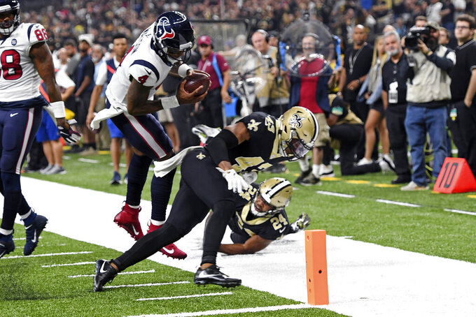 Houston Texans quarterback Deshaun Watson (4) scores a touchdown as he leaps over New Orleans Saints free safety Marcus Williams (43) and strong safety Vonn Bell (24) in the first half of an NFL football game in New Orleans, Monday, Sept. 9, 2019. (AP Photo/Bill Feig)