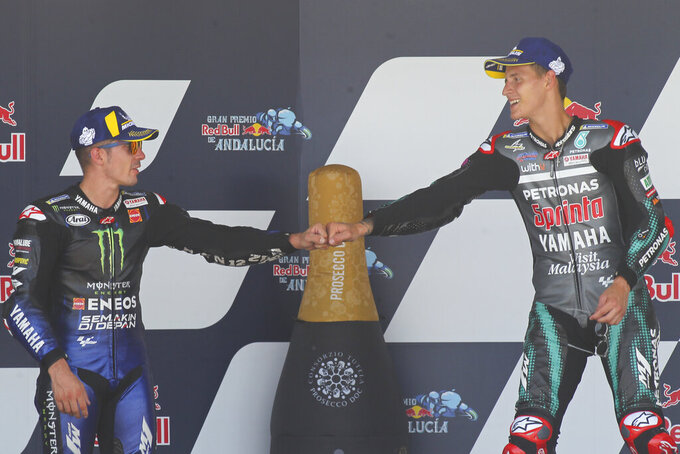 MotoGP race winner Fabio Quartararo of France, right, touches fists with 2nd placed Maverick Vinales of Spain during the MotoGP race during the Andalucia Motorcycle Grand Prix at the Angel Nieto racetrack in Jerez de la Frontera, Spain, Sunday July 26, 2020. (AP Photo/David Clares)