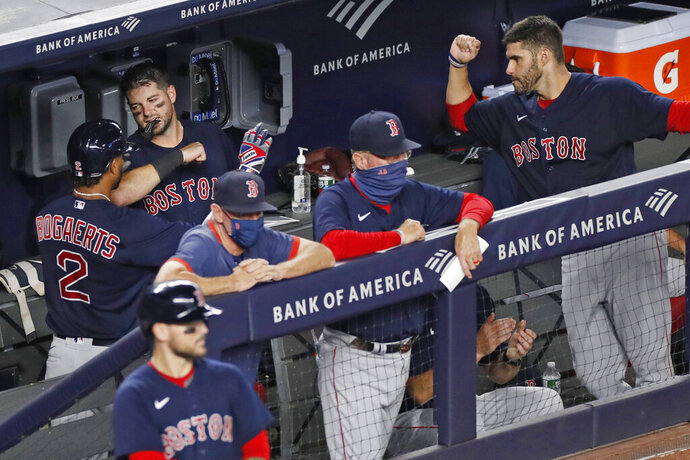 Boston Red Sox's Xander Bogaerts (2) celebrates with teammates in the dugout after hitting a fifth-inning solo home run in a baseball game against the New York Yankees, Sunday, Aug. 2, 2020, at Yankee Stadium in New York. (AP Photo/Kathy Willens)