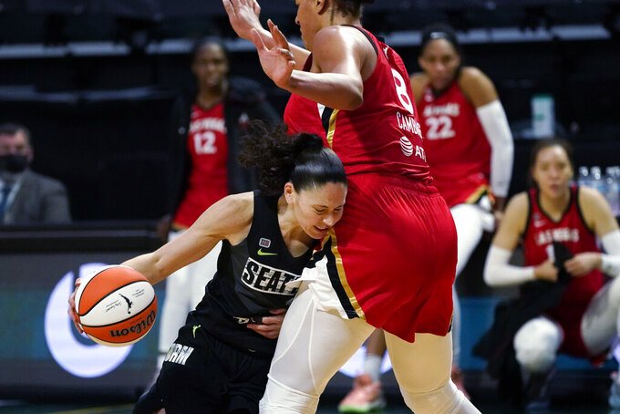 Seattle Storm's Sue Bird, left, runs into Las Vegas Aces' Liz Cambage in the second half of a WNBA basketball game Saturday, May 15, 2021, in Everett, Wash. Bird briefly left the game with an apparent injury on the play, but returned later in the game. The Storm won 97-83. (AP Photo/Elaine Thompson)
