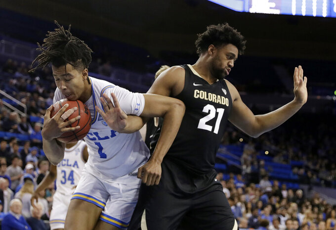UCLA center Moses Brown (1) grabs a rebound next to Colorado forward Evan Battey (21) during the first half of an NCAA college basketball game Wednesday, Feb. 6, 2019, in Los Angeles. (AP Photo/Marcio Jose Sanchez)