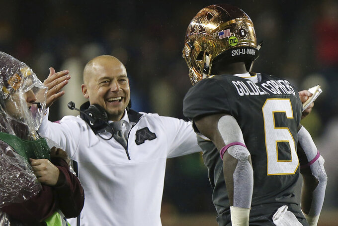 FILE - In this Oct. 26, 2018, file photo, Minnesota head coach P.J. Fleck greets wide receiver Tyler Johnson after the team scored against Indiana during an NCAA college football game, in Minneapolis. Minnesota has extended football coach P.J. Fleck's contract again by one year, through the 2023 season. The university announced the agreement on Friday, Dec. 14, 2018, after it was approved by the Board of Regents. (AP Photo/Stacy Bengs, File)
