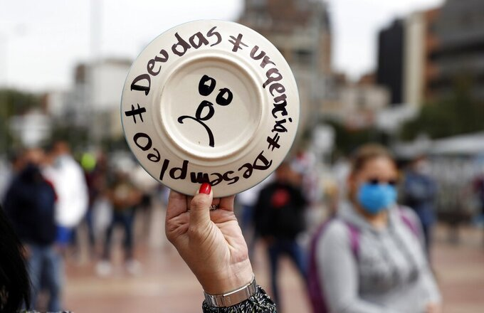 """A plate reads in Spanish """"Debts. Urgency. Unemployment,"""" as restaurant and bar workers break plates to protest the nighttime lockdown that forces them to close early during the COVID-19 pandemic in Bogota, Colombia, Monday, April 26, 2021. (AP Photo/Fernando Vergara)"""