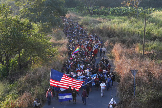 Central American migrants walk carrying a handmade U.S. flag and banners, after crossing the Suchiate River from Guatemala in Ciudad Hidalgo, Mexico, Thursday, Jan. 23, 2020. Hundreds of Central American migrants hoping to reach the United States marooned in Guatemala walked en masse across the river leading to Mexico in a second attempt to convince authorities there to allow them passage through the country. (AP Photo/Marco Ugarte)