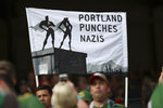A sign is held up before an MLS soccer match between the Portland Timbers and the Seattle Sounders on Friday, Aug. 23, 2019, in Portland, Ore. Major League Soccer recently instituted a policy that bans political displays at matches. (Serena Morones/The Oregonian via AP)