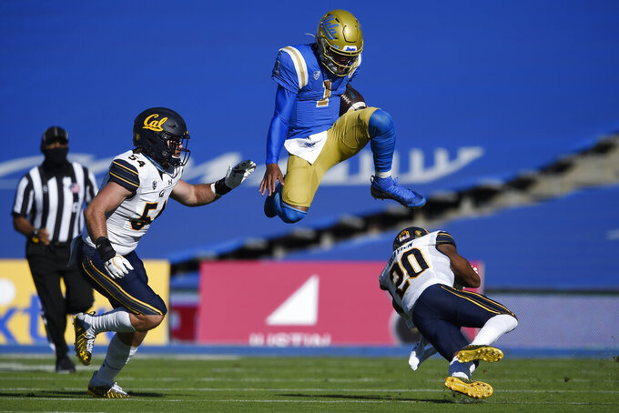 UCLA quarterback Dorian Thompson-Robinson, center, leaps over California cornerback Josh Drayden, right, on a run during the first half of an NCAA college football game as Evan Tattersall looks on in Los Angeles, Sunday, Nov. 15, 2020. (AP Photo/Kelvin Kuo)