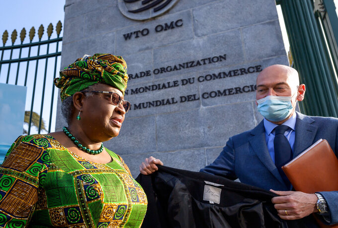 FILE - In this Monday, March 1, 2021 file photo, New Director-General of the World Trade Organisation Ngozi Okonjo-Iweala, left, walks at the entrance of the WTO, following a photo-op upon her arrival at the WTO headquarters to take office in Geneva, Switzerland. Ambassadors from World Trade Organization countries were discussing trade rules protecting the technological know-how behind COVID-19 vaccines. The WTO's General Council's agenda for a two-day meeting starting Wednesday, May 5, 2021 includes a waiver on intellectual property protections for vaccines. (Fabrice Coffrini/Pool/Keystone via AP, FIle)