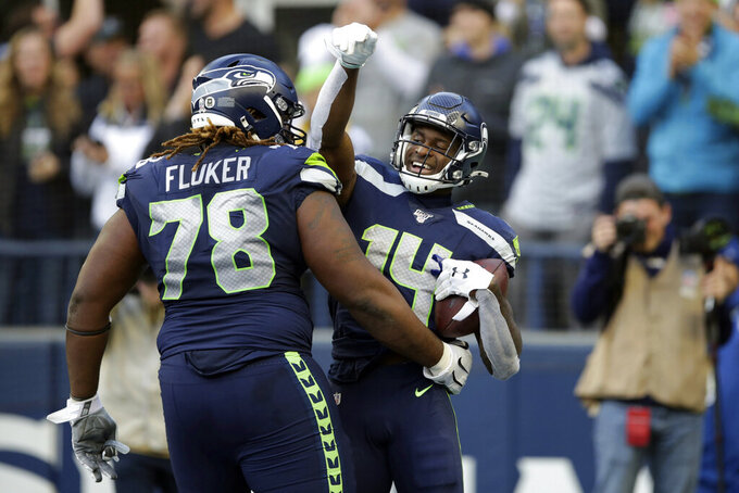 Seattle Seahawks wide receiver DK Metcalf, right, celebrates with D.J. Fluker (78) after scoring a touchdown against the Tampa Bay Buccaneers during the second half of an NFL football game, Sunday, Nov. 3, 2019, in Seattle. (AP Photo/Scott Eklund)