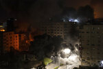 Smoke caused by Israeli airstrikes is seen on a residential building in Gaza City, early Wednesday, May 12, 2021. (AP Photo/Khalil Hamra)