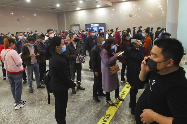 Travelers wearing masks line up to buy train tickets at a railway station in Yichang in central China's Hubei province Wednesday, March 25, 2020. Trains carrying factory employees back to work after two months in locked-down cities rolled out of Hubei province, the center of China's virus outbreak, as the government on Wednesday began lifting the last of the controls that confined tens of millions of people to their homes. (Chinatopix via AP)