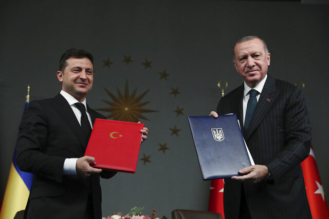 Turkish President Recep Tayyip Erdogan, right, and Ukrainian President Volodymyr Zelenskiy pose for photographs after they signed agreements, in Istanbul, Friday, Oct. 16, 2020. President Zelenskiy is in Istanbul for a one-day working visit. (Turkish Presidency via AP, Pool)