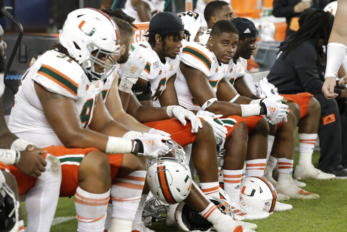 Miami players sit on the bench during the second half of the team's NCAA college football game against Florida International, Saturday, Nov. 23, 2019, in Miami. FIU won 30-24. (AP Photo/Lynne Sladky)