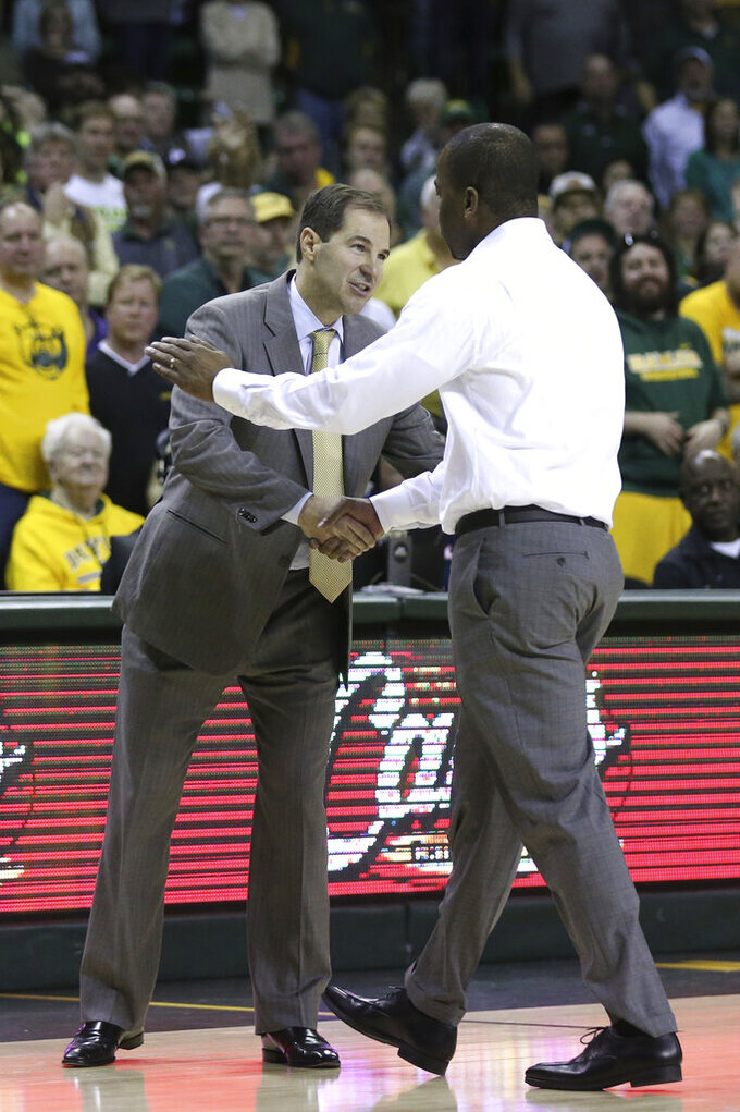 Baylor coach Scott Drew, left, shakes hands with Oklahoma State coach Mike Boynton, right, after Boynton was ejected during the second half of an NCAA college basketball game Saturday, Feb. 8, 2020, in Waco, Texas. (AP Photo/Rod Aydelotte)