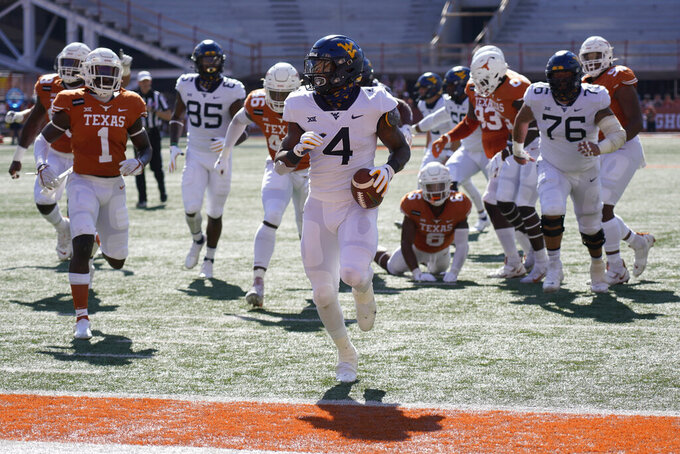 West Virginia's Leddie Brown (4) runs into the end zone for a touchdown against Texas during the first half of an NCAA college football game in Austin, Texas, Saturday, Nov. 7, 2020. (AP Photo/Chuck Burton)