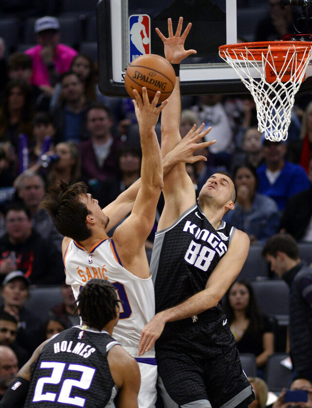 Phoenix Suns forward Dario Saric, center, goes to the basket against Sacramento Kings forward Nemanja Bjelica, right, during the first quarter of an NBA basketball game in Sacramento, Calif., Saturday, Dec. 28, 2019. (AP Photo/Hector Amezcua)