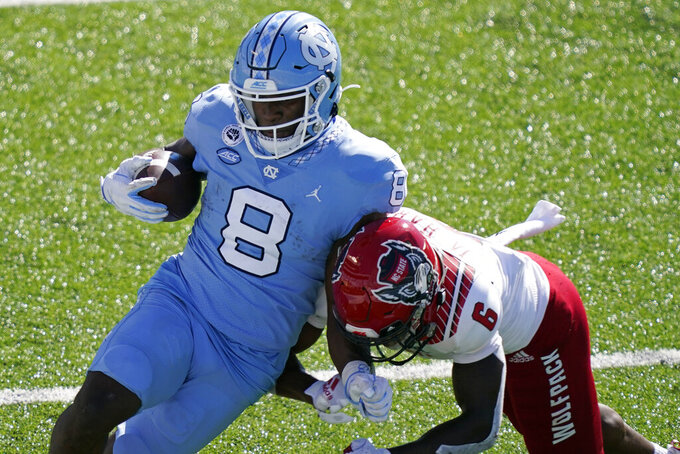 North Carolina running back Michael Carter (8) runs the ball while North Carolina State safety Jakeen Harris (6) makes the hit during the first half of an NCAA college football game in Chapel Hill, N.C., Saturday, Oct. 24, 2020. (AP Photo/Gerry Broome)