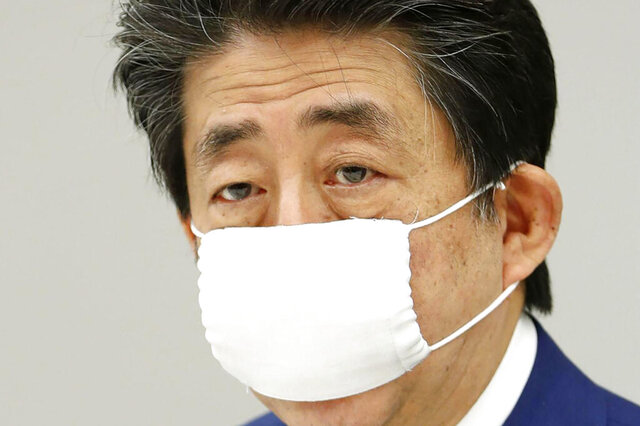 Japan's Prime Minister Shinzo Abe speaks during a meeting of the task force set up to curtail the new coronavirus outbreak, at his official residence in Tokyo Saturday, April 11, 2020. Japan has broadened a request for people to stay away from bars, clubs and restaurants across the whole country. (Kyodo News via AP)