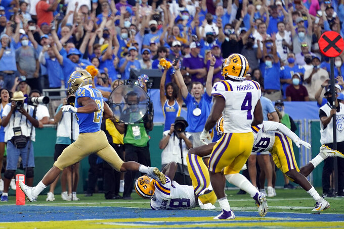 UCLA running back Zach Charbonnet, left, scores a touchdown as LSU linebacker Damone Clark (18) hangs on during the first half of an NCAA college football game Saturday, Sept. 4, 2021, in Pasadena, Calif. (AP Photo/Marcio Jose Sanchez)