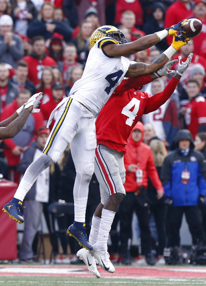 Michigan receiver Nico Collins, left, catches a pass in front of Ohio State defensive back Jordan Fuller during the second half of an NCAA college football game Saturday, Nov. 24, 2018, in Columbus, Ohio. Ohio State beat Michigan 62-39. (AP Photo/Jay LaPrete)