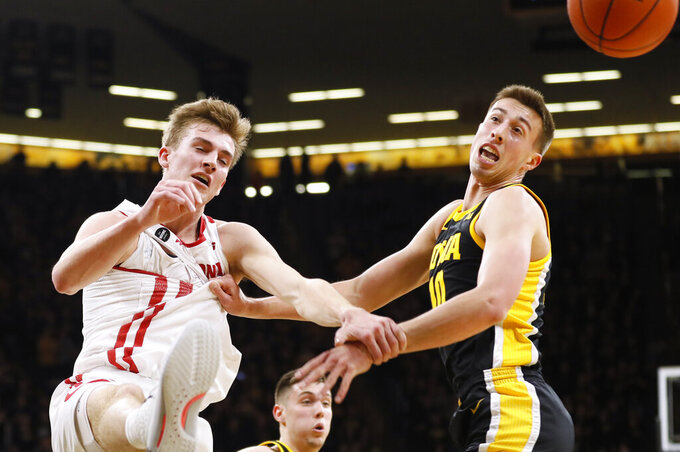 Wisconsin forward Tyler Wahl, left, fights for a rebound with Iowa guard Joe Wieskamp during the first half of an NCAA college basketball game, Monday, Jan. 27, 2020, in Iowa City, Iowa. (AP Photo/Charlie Neibergall)