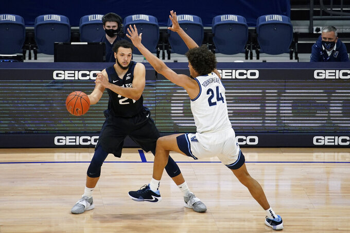 Butler's JaKobe Coles (21) tries to pass around Villanova's Jeremiah Robinson-Earl (24) during the first half of an NCAA college basketball game, Wednesday, Dec. 16, 2020, in Villanova, Pa. (AP Photo/Matt Slocum)