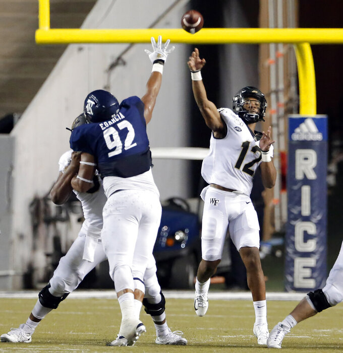 Wake Forest quarterback Jamie Newman (12) throws a pass as Rice defensive lineman Elijah Garcia (92) defends during the second half of an NCAA college football game Friday, Sept. 6, 2019, in Houston. (AP Photo/Michael Wyke)