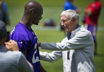In this June 18, 2015, photo, Former Minnesota Vikings coach Jerry Burns greets Adrian Peterson after practice at the NFL football team's minicamp in Eden Prairie, Minn. Burns, the colorful character who took over as the Vikings' head coach in a time of turmoil and led the team to three playoff berths, has died. He was 94. The team announced Burns' death. Vikings spokesman Bob Hagan said Burns' son-in-law informed him of Burns' death Wednesday morning, May 12, 2021. (Brian Peterson/Star Tribune via AP)