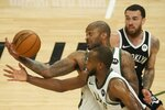 Milwaukee Bucks' P.J. Tucker and Khris Middleton steal the ball from Brooklyn Nets' Mike James during the first half of Game 4 of the NBA Eastern Conference basketball semifinals game Sunday, June 13, 2021, in Milwaukee. (AP Photo/Morry Gash)