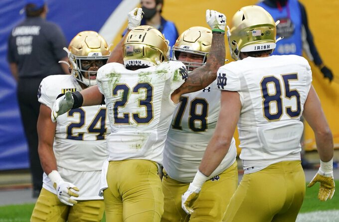 Notre Dame running back Kyren Williams (23) celebrates with teammates George Takacs (85), Tommy Kraemer (78) and Tommy Tremble (24) after scoring a touchdown against Pittsburgh during the first half of an NCAA college football game, Saturday, Oct. 24, 2020, in Pittsburgh. (AP Photo/Keith Srakocic)