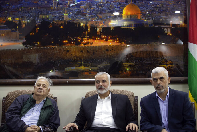 Yahya Sinwar, right, the Hamas militant group's leader in the Gaza Strip, sits with the  Hamas movement chief, Ismail Haniyeh, center, as they meet the Head of the Central Elections Commission, Hanna Nasser,  in Gaza City, Monday, Oct. 28, 2019. The militant Hamas group that runs the Gaza Strip says it's ready to go for Palestinian elections. (AP Photo/Khalil Hamra)