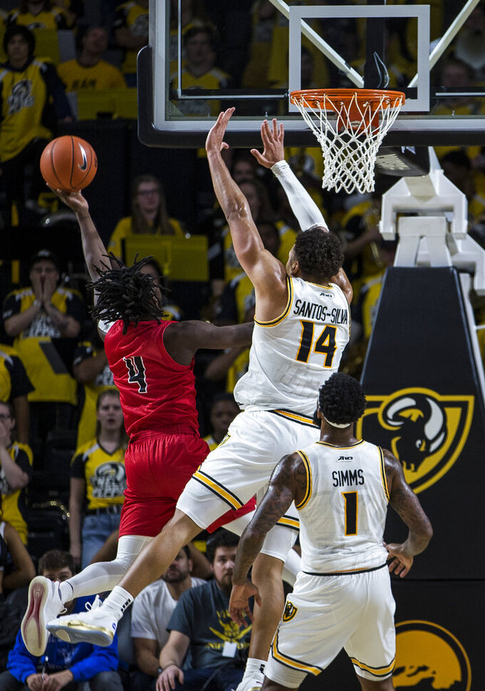 Jacksonville State point guard Ty Hudson (4) shoots as Virginia Commonwealth forward Marcus Santos-Silva (14) reaches to block during the second half of an NCAA college basketball game Sunday, Nov. 17, 2019, in Richmond, Va. (AP Photo/Zach Gibson)