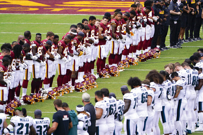 Members of the Washington Football Team and Philadelphia Eagles lock arms and form an oval on the field before the start of an NFL football game, Sunday, Sept. 13, 2020, in Landover, Md. (AP Photo/Susan Walsh)