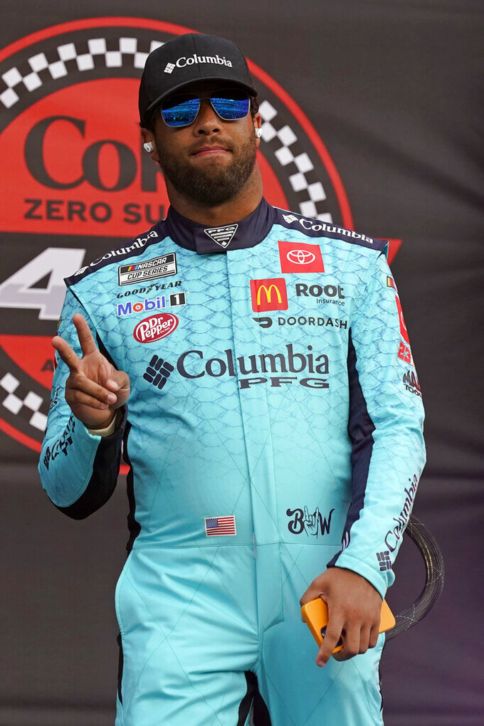 Bubba Wallace waves to fans during driver introductions before the NASCAR Cup Series auto race at Daytona International Speedway, Saturday, Aug. 28, 2021, in Daytona Beach, Fla. (AP Photo/John Raoux)