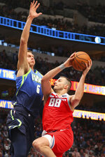 Dallas Mavericks forward Kristaps Porzingis (6) tries to defend against a shot by Sacramento Kings forward Nemanja Bjelica (88) in the second half of an NBA basketball game Sunday, Dec. 8, 2019, in Dallas. (AP Photo/Richard W. Rodriguez)
