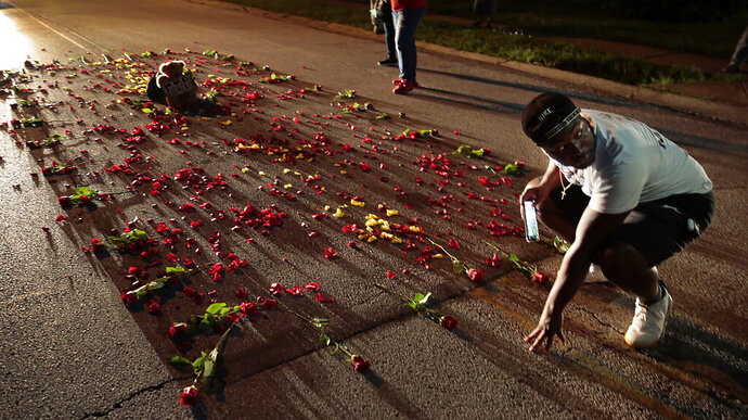 Donzell Clark photographs the rebuilt memorial for Michael Brown on Canfield Drive in Ferguson, Mo., on Thursday, July 30, 2020, at the spot where the teen was shot and killed by a Ferguson police officer in 2014.  St. Louis County's prosecutor announced Thursday that he will not charge the former police officer who fatally shot Michael Brown in Ferguson. (Robert Cohen /St. Louis Post-Dispatch via AP)