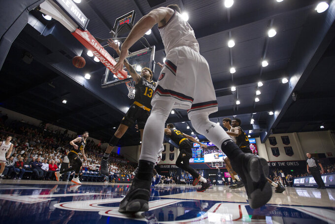 Saint Mary's guard Tommy Kuhse (12) inbounds the ball past Winthrop guard Hunter Hale (13) during the first half of an NCAA college basketball game, Monday, Nov. 11, 2019 in Moraga, Calif. (AP Photo/D. Ross Cameron)