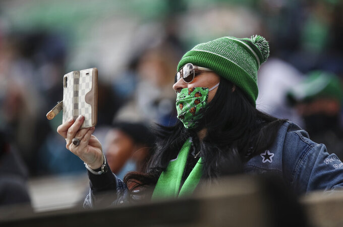A Marshall fan films the opening kickoff of an NCAA college football game on Saturday, Dec. 5, 2020, in Huntington, W.Va.  (Sholten Singer/The Herald-Dispatch via AP)