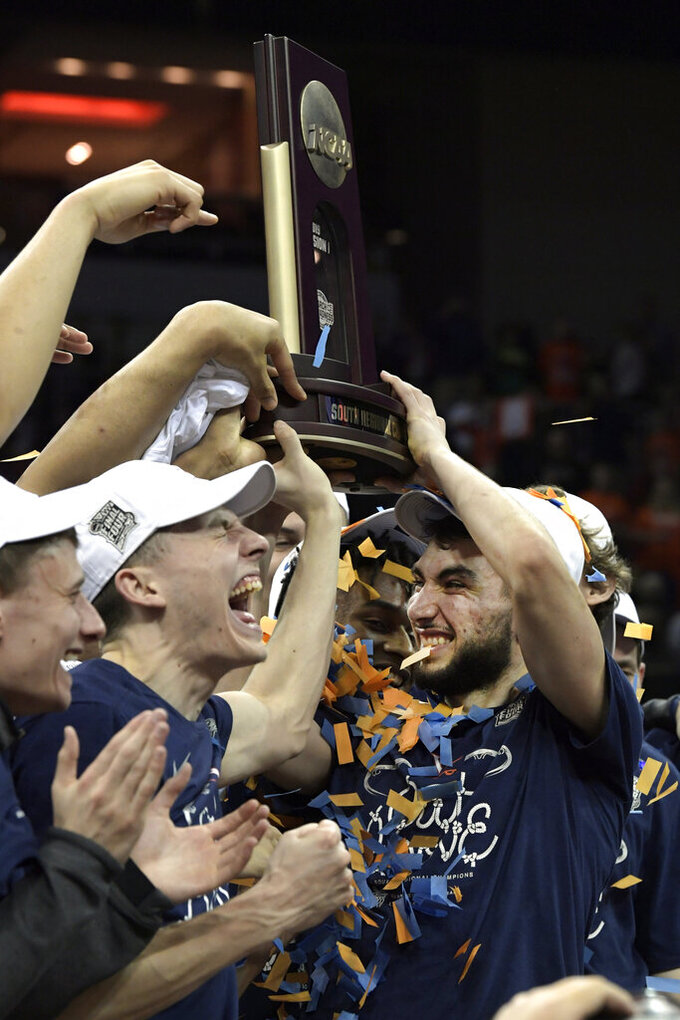 Members of Virginia celebrate after defeating Purdue 80-75 in overtime of the men's NCAA Tournament college basketball South Regional final game, Saturday, March 30, 2019, in Louisville, Ky. (AP Photo/Timothy D. Easley)